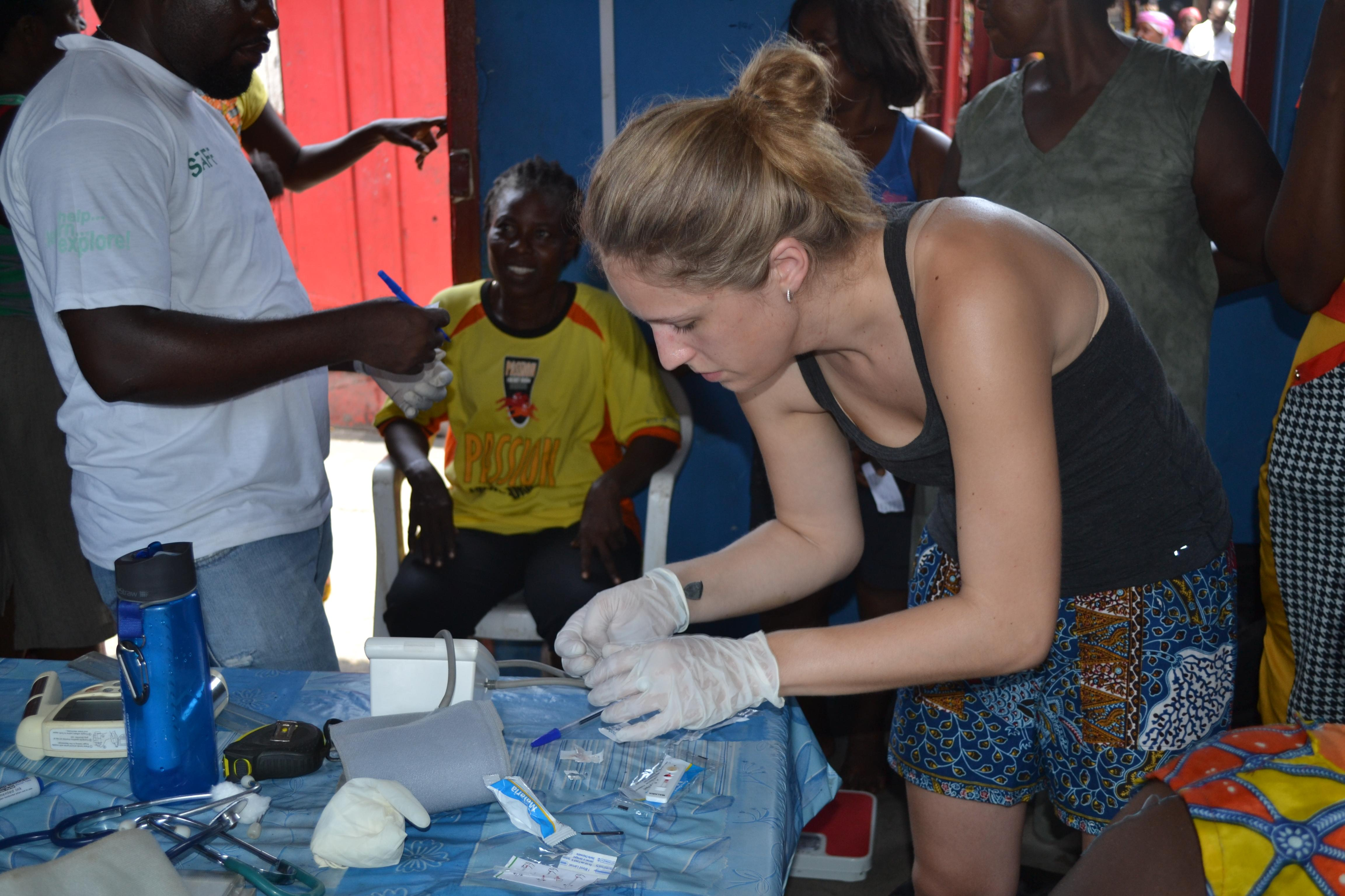 A medical outreach intern from Projects Abroad assisting in health check ups as part of her public health internship in Ghana.